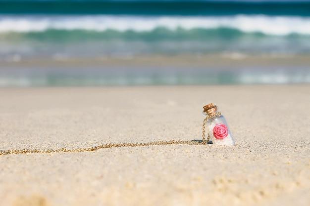Mała pamiątkowa butelka w białym piasku na turkusowym morzu