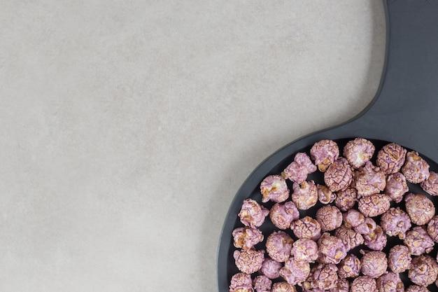 Mała patelnia z aromatyzowanym popcornem na marmurowym stole.