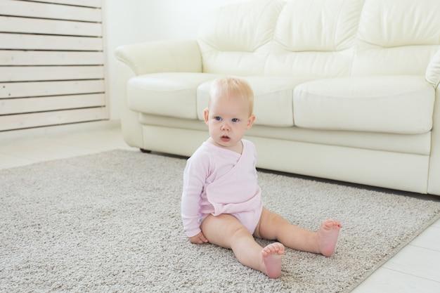 Mała pełzająca dziewczynka jeden rok siedzi na podłodze w jasnym świetle salonu uśmiechnięty i