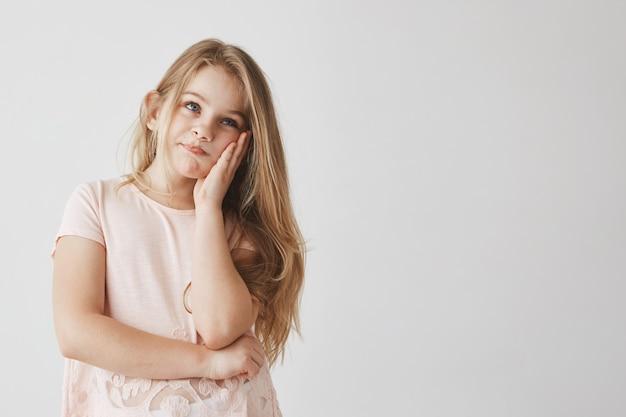 Mała piękna blondynka o niebieskich oczach ściskających twarz dłonią, patrząca na bok z sfrustrowanym wyrazem twarzy, gdy mama wie o złych znakach w szkole.
