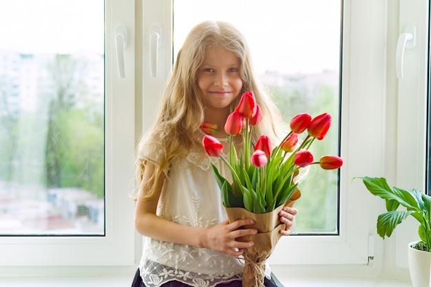 Mała piękna dziecko dziewczyna z bukietem czerwoni tulipany kwitnie