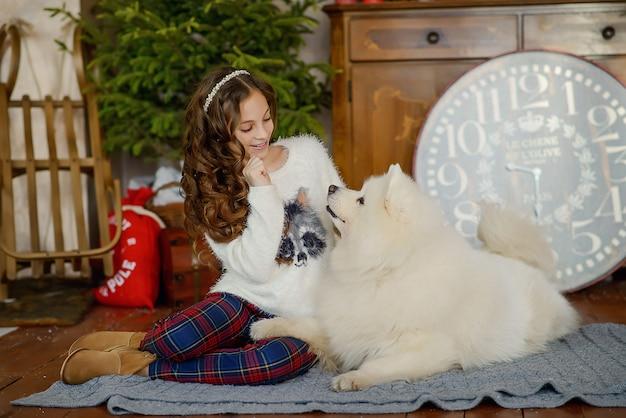 Mała, piękna dziewczyna i duży biały puszysty pies bawią się w noworoczne wnętrze bożego narodzenia.