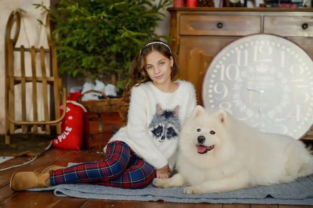 Mała piękna dziewczyna i duży biały puszysty pies obok choinki we wnętrzu nowego roku.