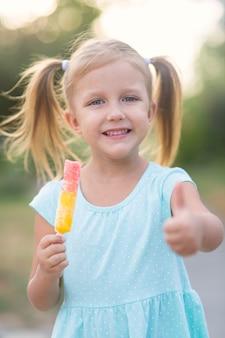 Mała piękna dziewczyna je na zewnątrz lody w parku