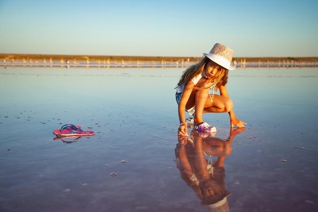 Mała piękna dziewczyna patrząca na coś w przezroczystej powierzchni wody na przezroczystym tle