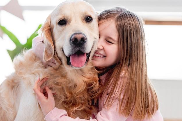 Mała piękna dziewczyna pieszczoty uroczego psa golden retriever