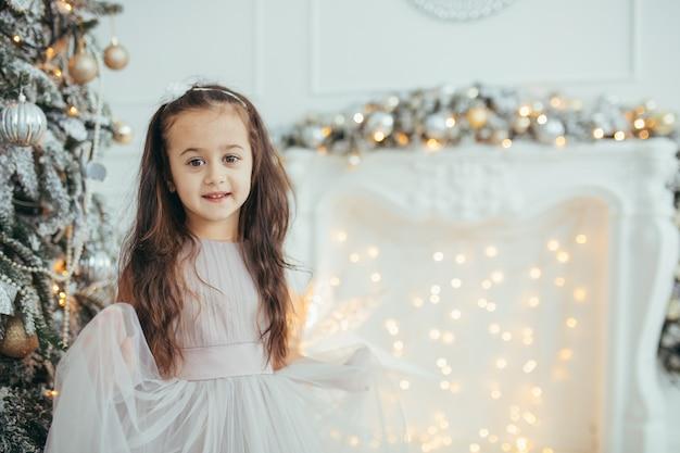 Mała piękna dziewczyna pozuje w świątecznym wystroju