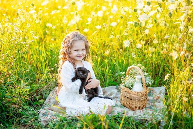 Mała piękna dziewczyna siedzi na trawniku latem z czarnym kotkiem