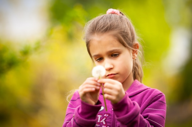 Mała piękna dziewczyna trzyma w ręku mniszek wiosna