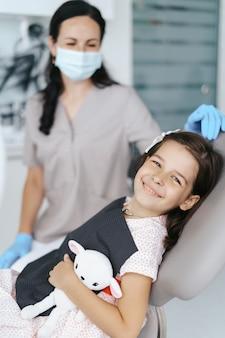 Mała piękna dziewczyna u dentysty, patrząc i uśmiechając się