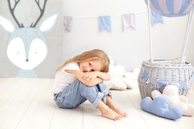 Mała piękna dziewczyna w białej koszulce i dżinsach siedzi z ozdobnym balonem. dziecko bawi się w pokoju dziecięcym. pojęcie dzieciństwa, podróż. dekoracja świąteczna z okazji urodzin