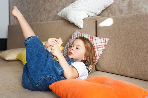 Mała piękna dziewczyna w niebieskim kombinezonie leży w domu na kanapie i dokładnie ogląda swoje nagie nogi