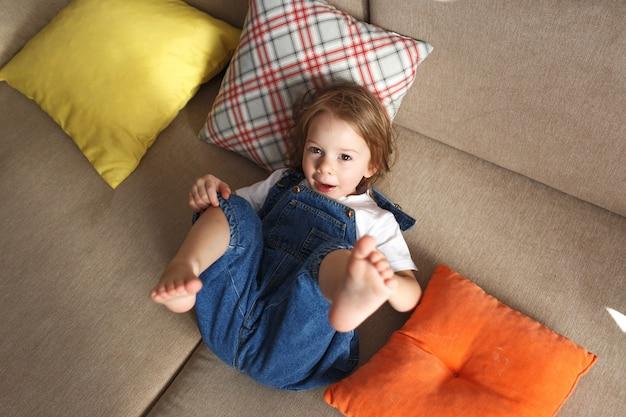 Mała piękna dziewczyna w niebieskim kombinezonie leży w domu na sofie z podniesionymi nogami, wokół wielu kolorowych poduszek