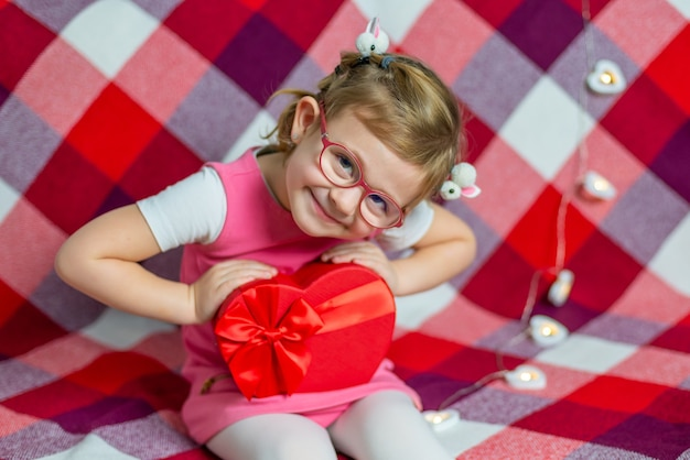 Mała piękna dziewczyna w okularach z czerwonym sercem pudełko i balon. święta walentynkowe.