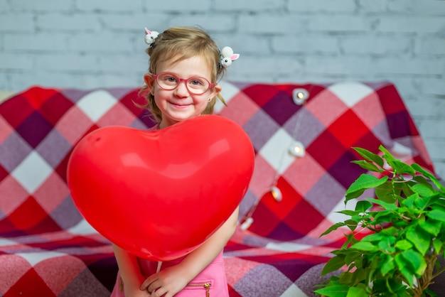 Mała piękna dziewczyna w okularach z czerwonym sercem pudełko i balon