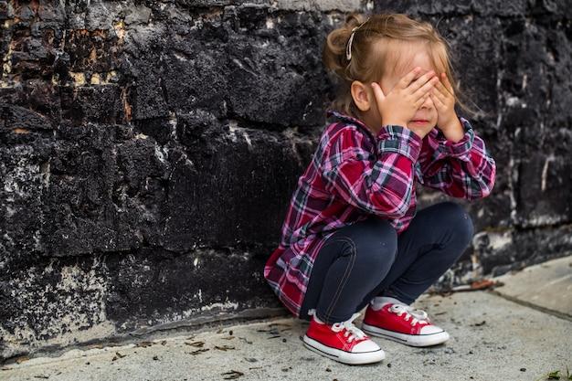 Mała piękna dziewczyna w pobliżu ściany z cegły