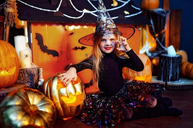Mała piękna dziewczyna w stroju wiedźmy świętuje w domu we wnętrzu z dyniami i magicznym domkiem z kartonu w tle