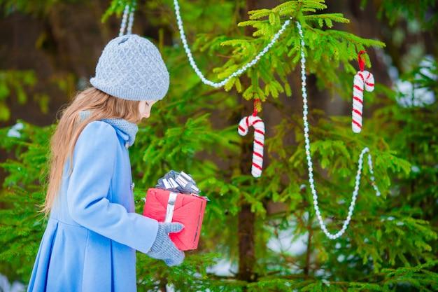 Mała piękna dziewczyna z bożymi narodzeniami boksuje prezent w zima dniu outdoors. nowy rok już wkrótce