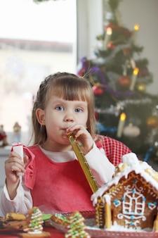 Mała piękna dziewczyna z domem ciasta piernikowego