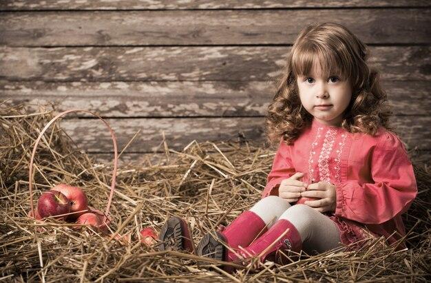 Mała piękna dziewczyna z jabłkami na starym drewnianym tle