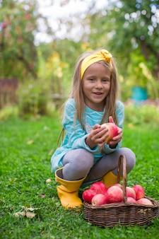 Mała piękna dziewczyna z koszem czerwoni jabłka