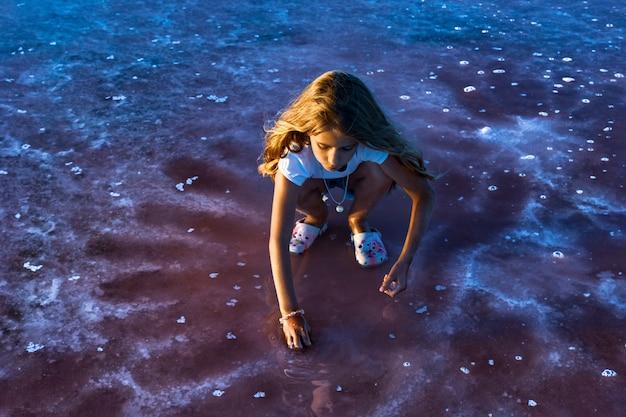 Mała piękna dziewczyna z pięknymi falującymi włosami patrzy na sól w przezroczystej wodnistej glazurze na przezroczystym tle