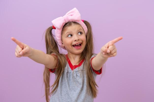 Mała piękna dziewczyna z różową kokardką na głowie uśmiecha się i wskazuje palcami na bok.