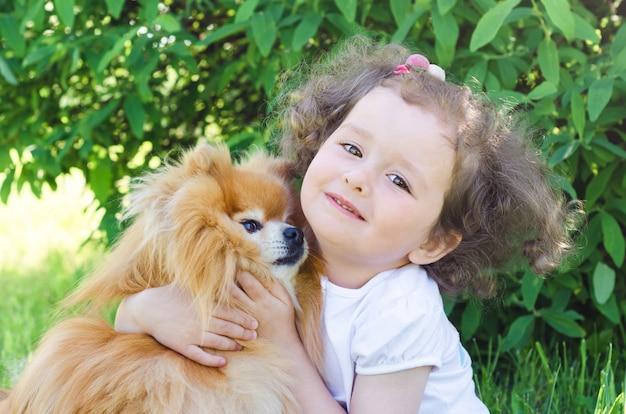 Mała piękna dziewczyna z zwierzęciem domowym na naturze. szczęśliwe dziecko przytulanie psa. kobieta bawi się szpicem pomorskim na zewnątrz.