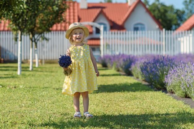 Mała piękna dziewczynka idzie przez szerokie fioletowe pole lawendy.
