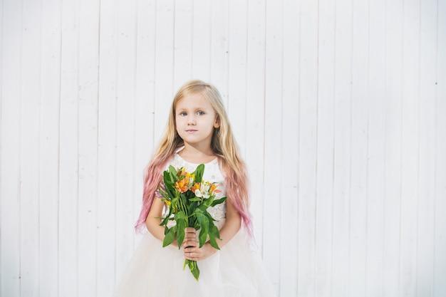 Mała piękna dziewczynka w pięknej sukience z bukietem kwiatów na białym drewnianym tle