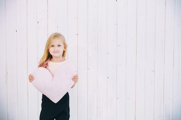 Mała piękna dziewczynka w wakacyjnej czapce i z poduszką w kształcie serca na białym drewnianym tle