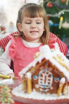 Mała piękna dziewczynka z domkiem z ciasta piernikowego