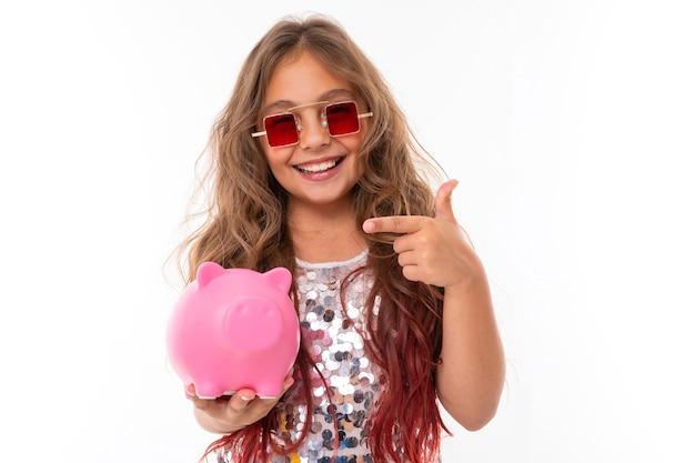 Mała piękna kaukaska dziewczyna z długimi falującymi kasztanowymi włosami i ładnym uśmiechem pokazuje swoją różową świnkę skarbonkę
