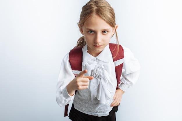 Mała piękna uczennica, z teczką, biała ściana