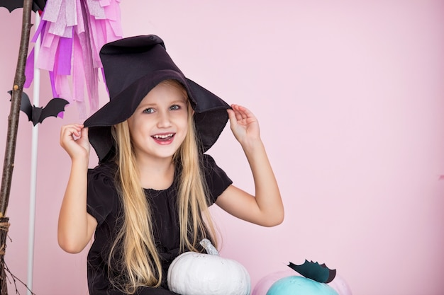 Mała piękna urocza dziewczynka w stroju karnawałowym czarownic w modnych dekoracjach na halloween