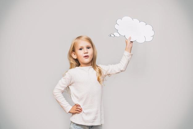 Mała piękna urocza dziewczynka z białą chmurą myśli w postaci znaku w studio na szarym tle