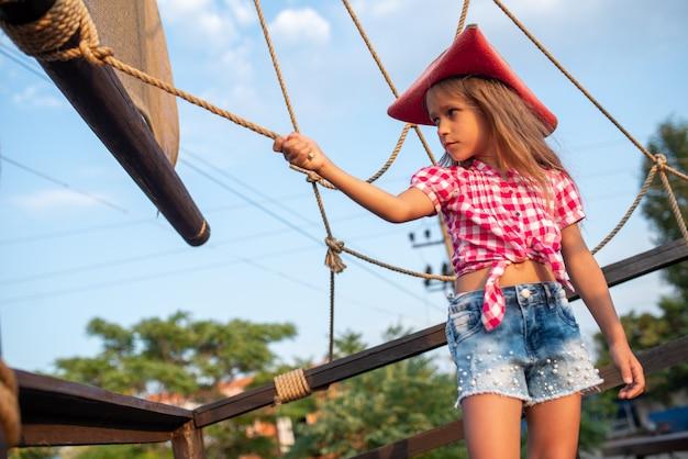Mała piratka w kraciastej koszuli i dżinsowych szortach trzyma się sznurów statku