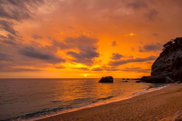Mała plaża między klifami na greckim wybrzeżu morza śródziemnego. wielokolorowy wschód słońca nad spokojną wodą