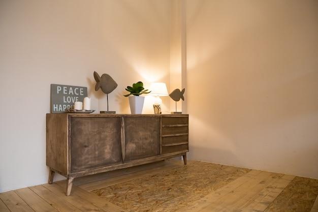 Mała płonąca lampa i mała roślina doniczkowa są umieszczone na skrzyni w salonie