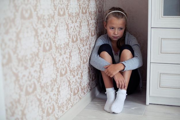 Mała pokrzywdzona dziewczyna siedzi w kącie pokoju