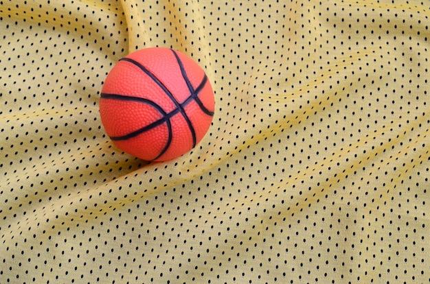 Mała pomarańczowa gumowa koszykówka kłama na żółtej sportowej dżersejowej odzieży tkaniny teksturze i tle z wiele fałdami