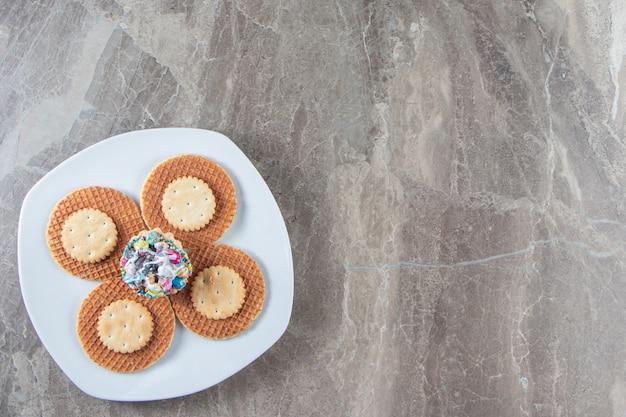 Mała porcja deseru na talerzu na marmurze.