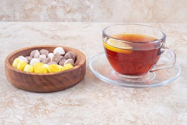 Mała porcja herbaty z plasterkiem cytryny i cukierkami