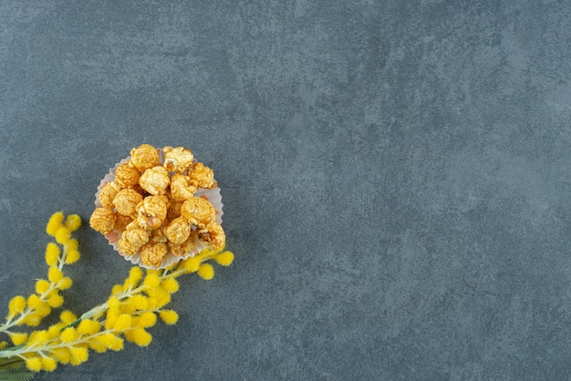 Mała porcja karmelowego popcornu obok łodygi wrażliwej rośliny na marmurowym tle. zdjęcie wysokiej jakości