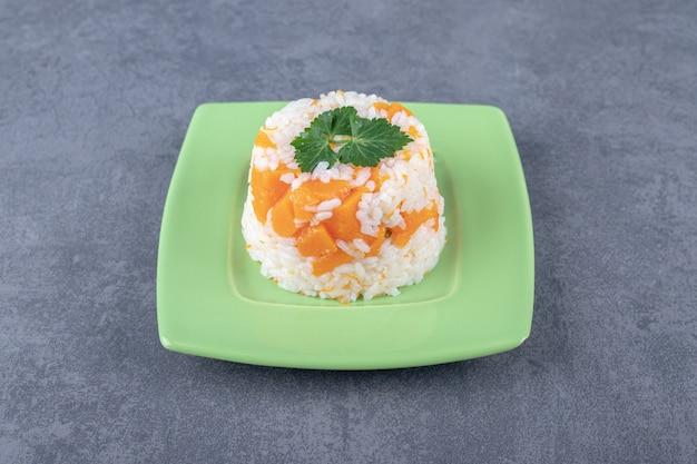 Mała porcja ryżu marchewkowego na marmurowej powierzchni.