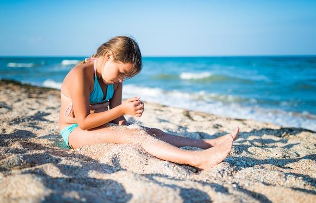 Mała pozytywna dziewczynka siedzi nad brzegiem morza i cieszy się morskimi falami w słoneczny letni dzień podczas wakacji