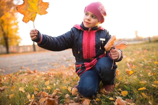 Mała pozytywna dziewczynka z liściem żółtych liści klonu spaceruje po parku w słoneczny, ciepły jesienny dzień