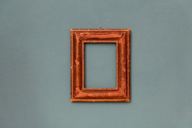 Mała prostokątna drewniana rama w stylu vintage wisząca pośrodku na ścianie w kolorze turkusowym