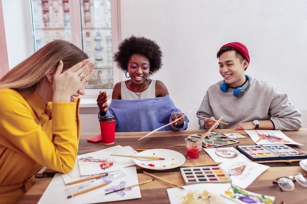Mała przerwa. trzech młodych obiecujących artystów śmiejących się podczas krótkiej przerwy w pracy