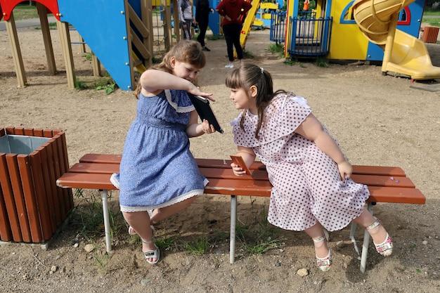 Mała pulchna dziewczyna z zadowolonym uśmiechem pokazuje drugiej dziewczynie coś na swoim tablecie
